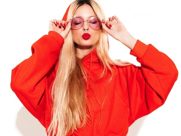 Retrato de menina má jovem hippie bonito no capuz vermelho na moda e brinco no nariz. modelo positivo se divertindo. isolado no branco