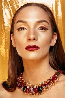 Retrato de menina mágica em ouro. maquiagem dourada, retrato de close-up em estúdio, cor. beauty model girl com maquiagem brilhante perfeita, lábios vermelhos, joias marrom dourado. festa de férias de maquiagem de senhora sexy.
