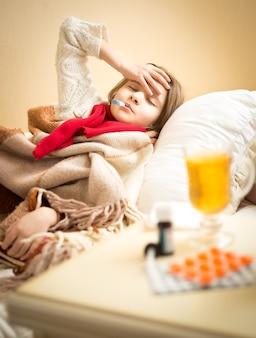Retrato de menina medindo temperatura e sofrendo de dor de cabeça