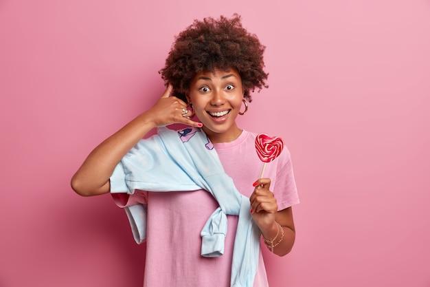 Retrato de menina milenar alegre e bonita faz gesto de telefonar, vestida com roupa casual, posa com pirulito, pede para ligar para ela, estando de bom humor, fica dentro de casa