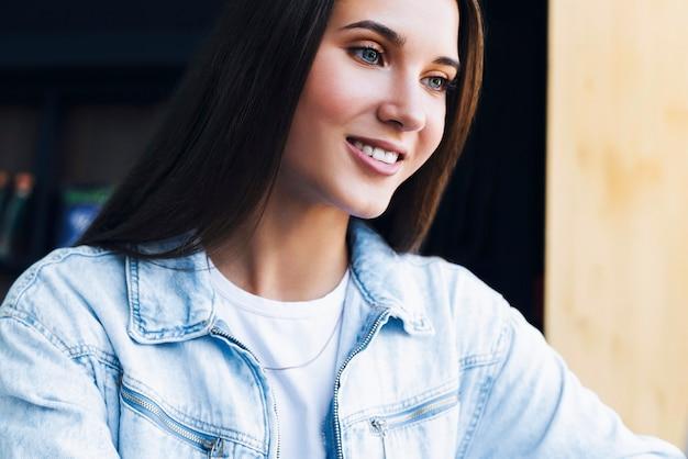 Retrato de menina milenar em camisa jeans em posição confortável.