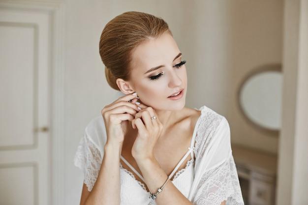 Retrato de menina modelo loira com olhos fechados e maquiagem suave no interior