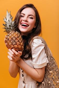 Retrato de menina morena de excelente humor, segurando o abacaxi e o saco de barbante em fundo laranja.