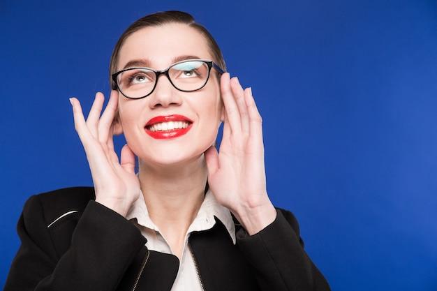 Retrato de menina morena de óculos com as mãos perto do rosto
