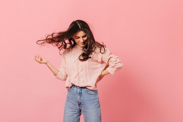 Retrato de menina morena em alto astral jogando cabelo. garota de suéter e jeans está se divertindo no fundo rosa.