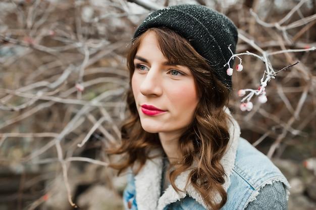 Retrato de menina morena em jaqueta jeans e chapéu em arbustos congelados.