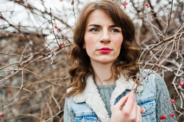 Retrato de menina morena em jaqueta jeans em arbustos congelados.
