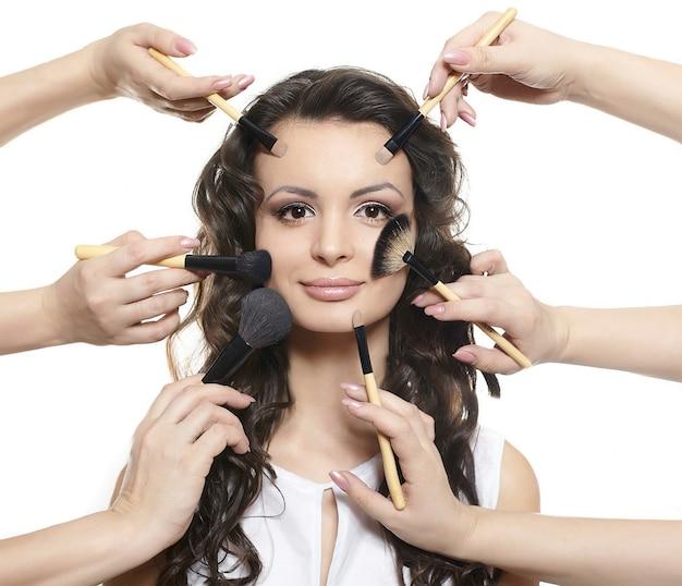 Retrato de menina morena longo cabelo ondulado e encaracolado bonito com pincéis de maquiagem perto do rosto atraente, muitas mãos se aplicam maquiagem no rosto de mulher isolado no branco