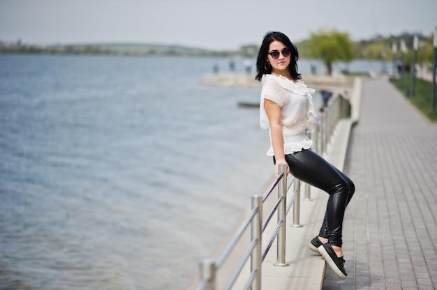 Retrato de menina morena nas calças de couro das mulheres e blusa branca, óculos de sol, contra trilhos de ferro na praia.