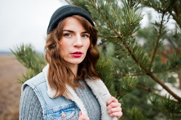 Retrato de menina morena no chapéu e jaqueta jeans na árvore.