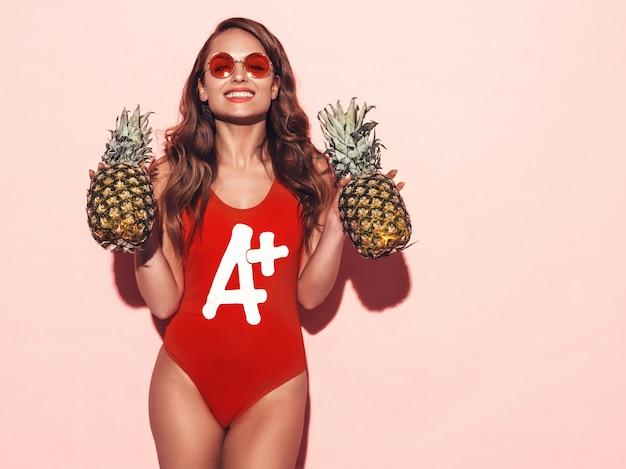 Retrato de menina morena sorridente em roupas de banho vermelho verão e óculos de sol redondos. mulher sexy com abacaxis frescos. posando modelo positivo