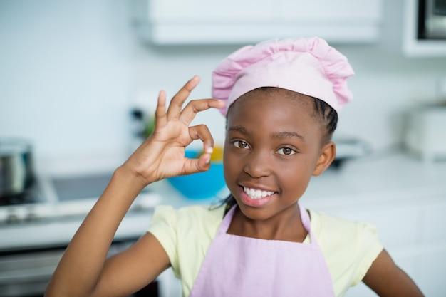 Retrato de menina mostrando a mão ok cadastre-se na cozinha