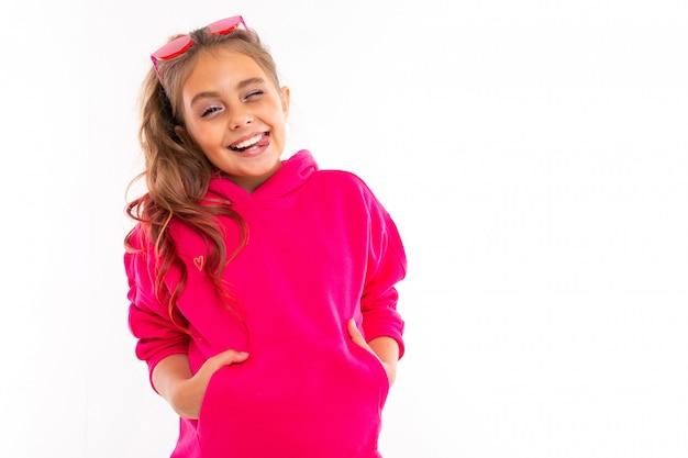 Retrato de menina na moda em moletom rosa, óculos de sol rosa é feliz e mantém as mãos nos bolsos, isolados no branco