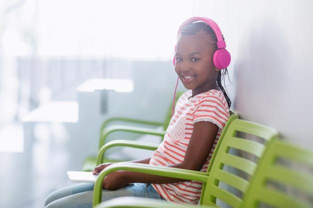 Retrato de menina ouvindo música do tablet digital