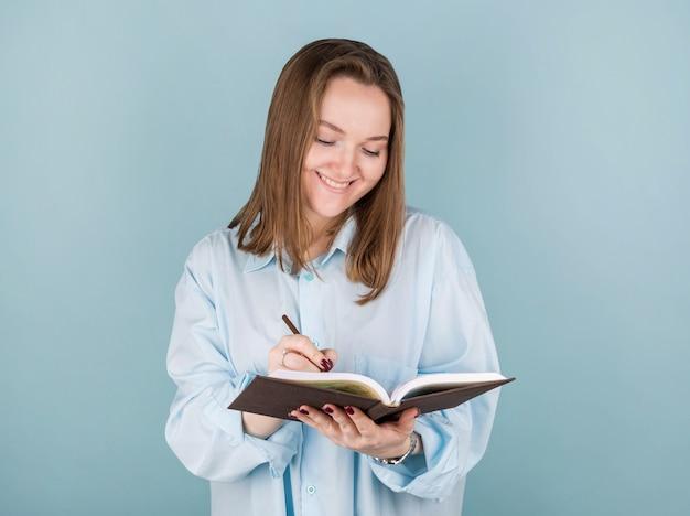 Retrato de menina pensativa pensativa, tendo o caderno e o lápis na boca. isolado em azul com espaço de cópia.