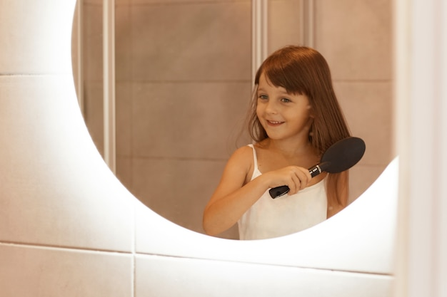 Retrato de menina penteando o cabelo no banheiro, fazendo procedimentos de beleza matinais sozinha em frente ao espelho, vestindo roupas de casa.