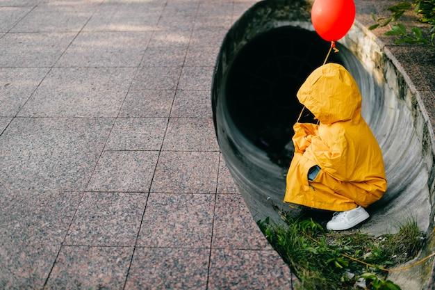 Retrato de menina pequena na capa de chuva amarela de grandes dimensões com balão vermelho na mão, sentado no tubo do túnel de esgoto