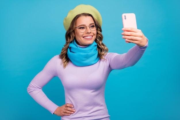 Retrato de menina positiva fazendo selfie em seu smartphone na parede azul-petróleo