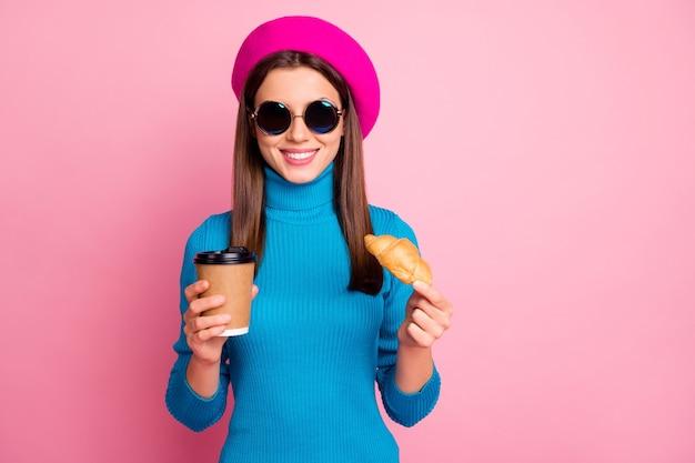 Retrato de menina positiva viajar cafeteria relaxar cafeteria segurar saboroso croissant de bebida café expresso caneca para viagem usar jumper de óculos de sol azul headwear.