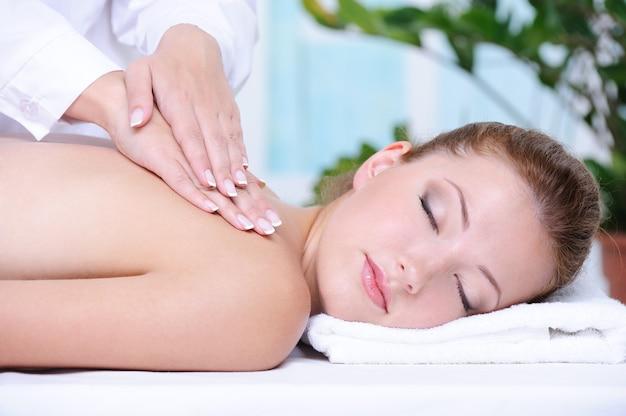Retrato de menina recebendo massagem e relaxamento nas costas no salão spa