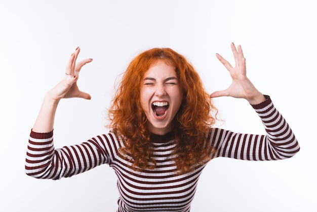 Retrato de menina ruiva agressiva de fúria, mãos levantadas e gritando com os olhos fechados