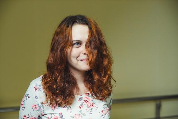 Retrato de menina ruiva alegre bonita com cabelos cacheados sobre parede verde-amarela.
