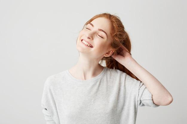 Retrato de menina ruiva bonita jovem feliz sorrindo com os olhos fechados, tocando o cabelo.
