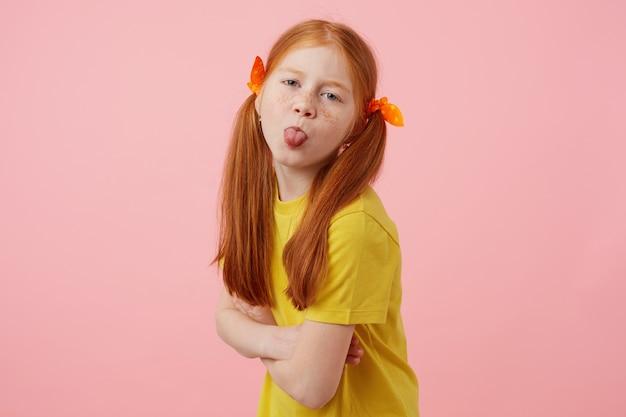 Retrato de menina ruiva de petite sardas com duas caudas, parece e mostra a língua para a câmera, usa uma camiseta amarela, fica sobre fundo rosa.