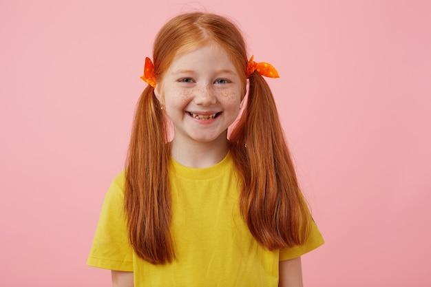 Retrato de menina ruiva feliz petite sardas com duas caudas, amplamente sorrindo e parece fofo, usa uma camiseta amarela, fica sobre fundo rosa.