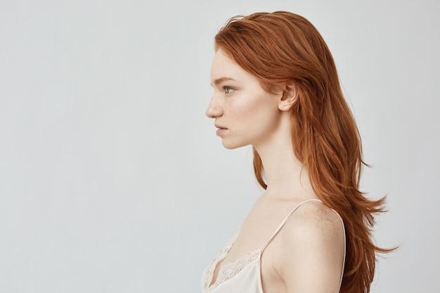 Retrato de menina ruiva linda posando no perfil.