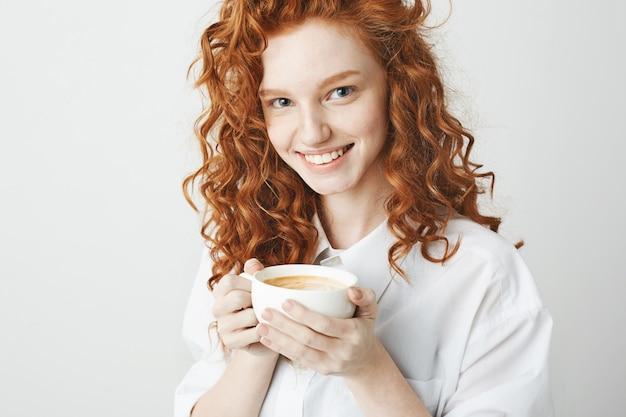 Retrato de menina ruiva macia com sardas sorrindo segurando xícara