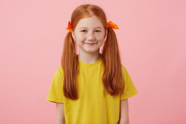 Retrato de menina ruiva petite sardas com duas caudas, olha para a câmera e sorri, usa uma camiseta amarela, fica sobre fundo rosa.