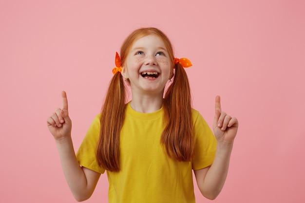 Retrato de menina ruiva sorridente petite sardas com duas caudas, olha e poits para cima nos espaços de cópia, usa em t-shirt amarela, fica sobre fundo rosa.