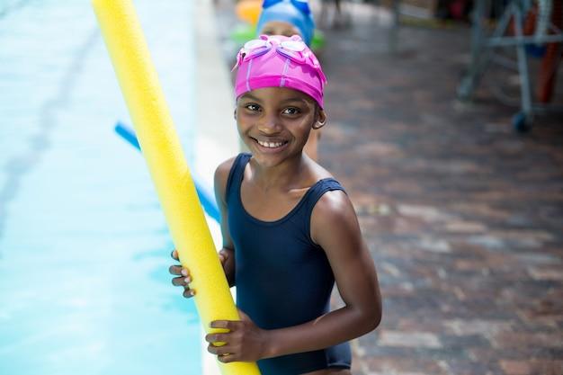 Retrato de menina segurando macarrão à beira da piscina