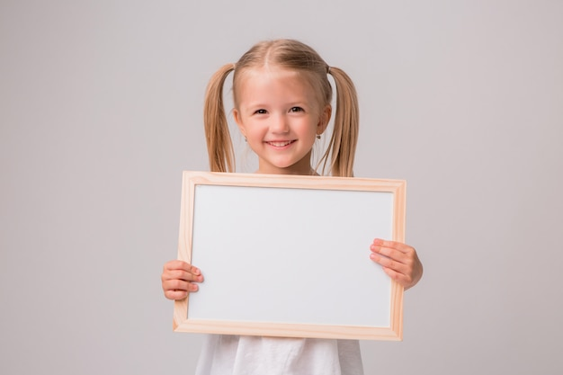Retrato de menina segurando o quadro de desenho branco sobre fundo branco