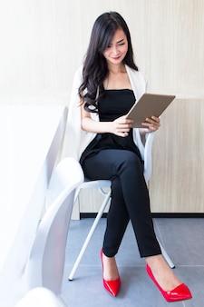 Retrato de menina segurando o tablet. meninas de terno branco e preto para compras on-line.
