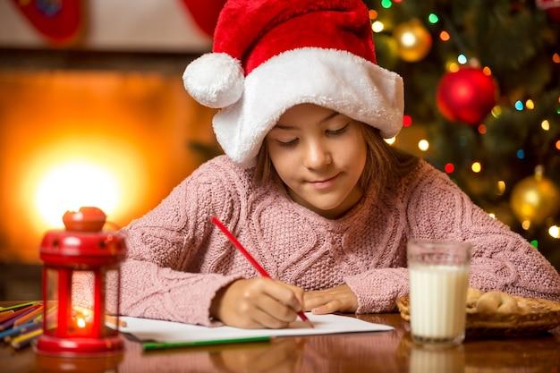 Retrato de menina sentada na lareira e escrevendo uma carta para o papai noel