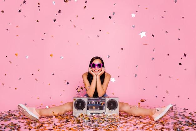Retrato de menina sentada no chão de boombox esperar confete cair parede rosa isolada