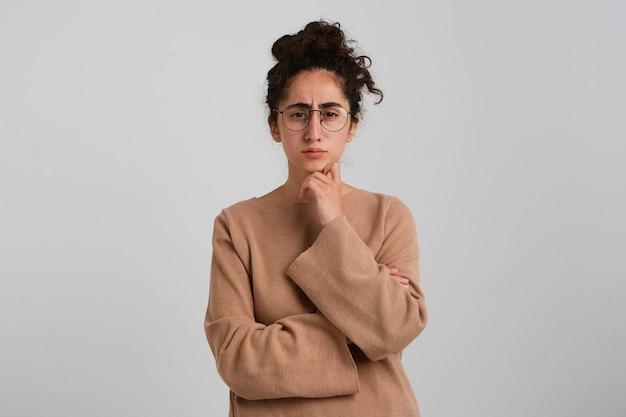 Retrato de menina séria e adulta com coque de cabelo encaracolado escuro, vestindo macacão bege e óculos