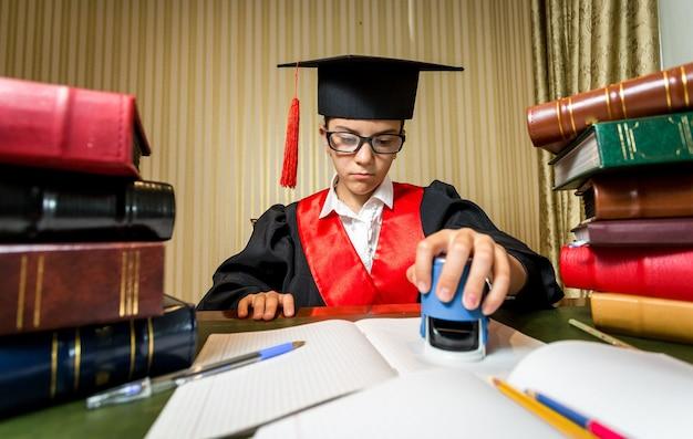 Retrato de menina séria e inteligente no chapéu da formatura, brincando de advogado e colocando o carimbo no documento