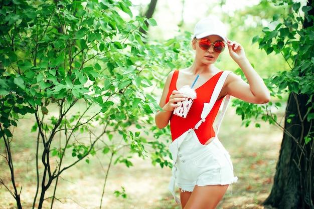 Retrato de menina sexy moda elegante usando óculos de sol arredondados maiô vermelho branco boné de beisebol ...