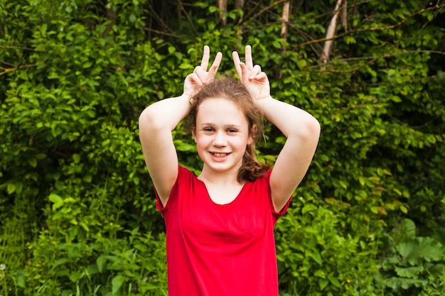 Retrato, de, menina sorridente, arreliando, com, dedo, mão, parque