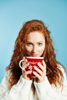 Retrato de menina sorridente bebendo chá quente