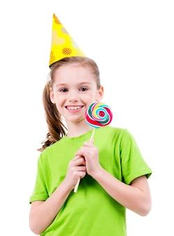 Retrato de menina sorridente com camiseta verde e chapéu de festa com doces coloridos - isolado no branco