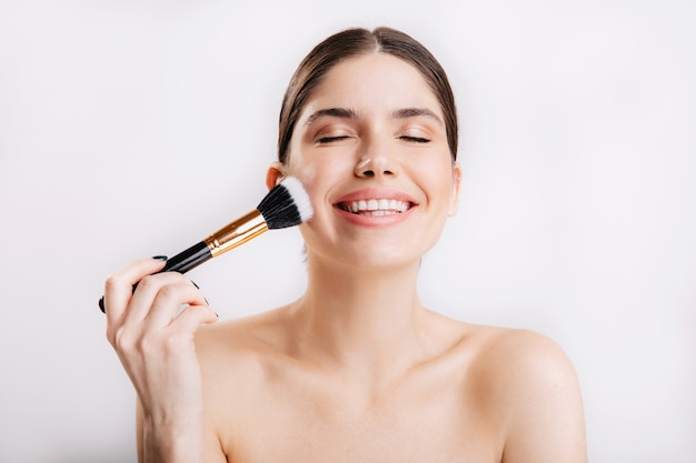 Retrato de menina sorridente com pele limpa, aplicando o pincel de pó no rosto contra uma parede isolada.