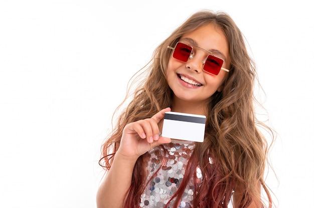 Retrato de menina sorridente em óculos de sol quadrados vermelhos, segurando o cartão de banco plástico isolado