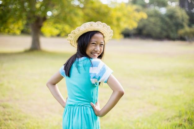 Retrato de menina sorridente em pé com mão no quadril no parque
