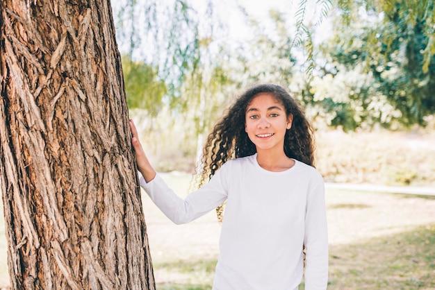 Retrato, de, menina sorridente, ficar, perto, a, árvore, olhando câmera