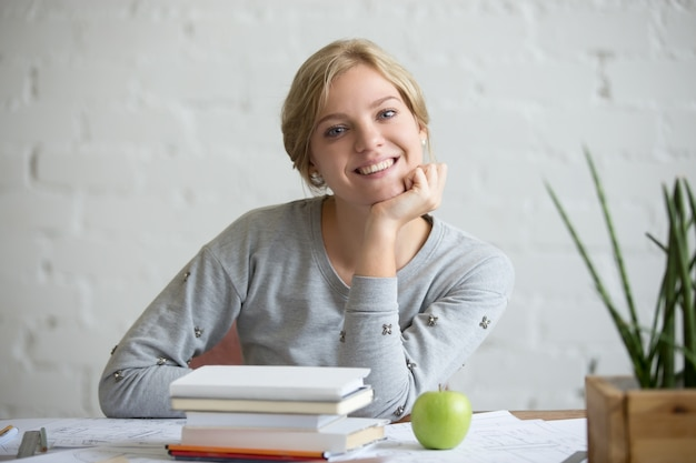 Retrato de menina sorridente na mesa com livros e maçã