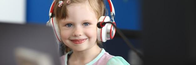 Retrato de menina sorridente, olhando para a câmera com alegria e calma. bebê feliz jogando jogos de computador. gracinha no local de trabalho do pai. conceito de infância e nova geração